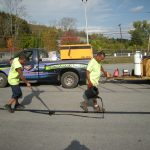 Crew applying sealcoating to large parking lot