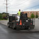 Asphalt paving crew on back of truck with paving equipment